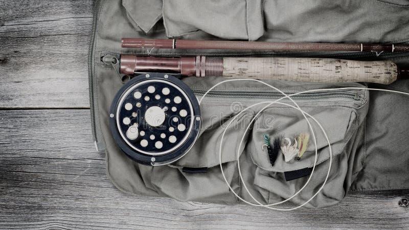 Artes de pesca velhas da truta sobre a veste da pesca fotografia de stock