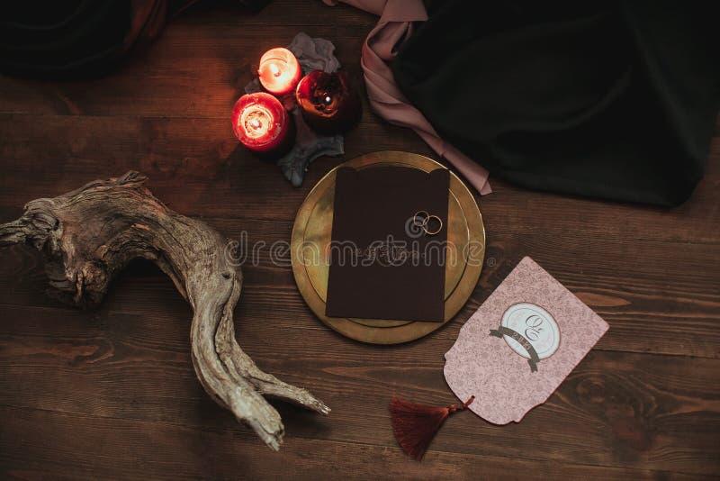 Artes gráficos de la boda hermosa rosados y tarjetas marrones, placa de oro con dos anillos, velas, tela, gancho en la madera foto de archivo libre de regalías