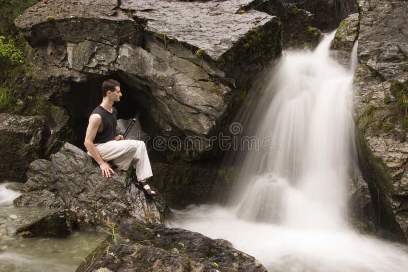 Artes marciales - meditación al lado de la cascada fotos de archivo libres de regalías