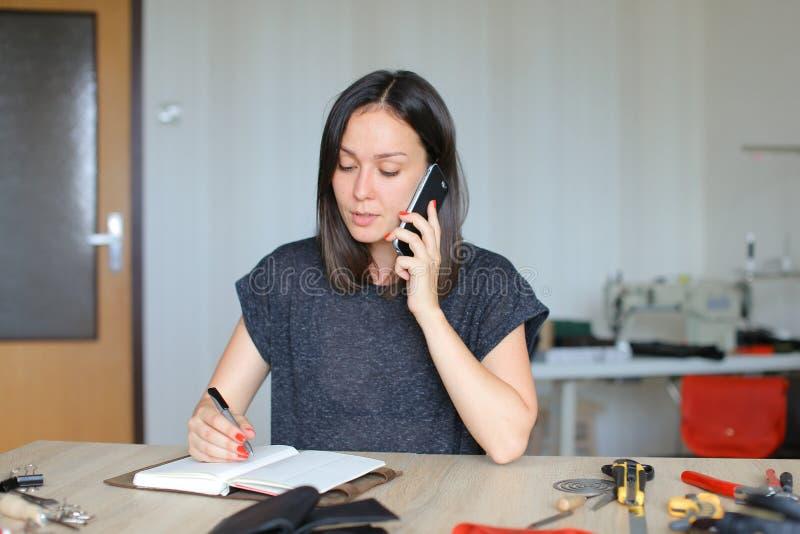 Artesana caucásica que habla por smartphone y que anota en cuaderno de cuero hecho a mano en casa foto de archivo libre de regalías