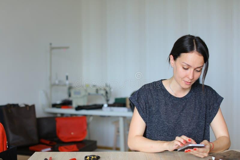 Artesana europea que se sienta en el taller y que usa el smartphone, mercancías de cuero hechas a mano fotografía de archivo