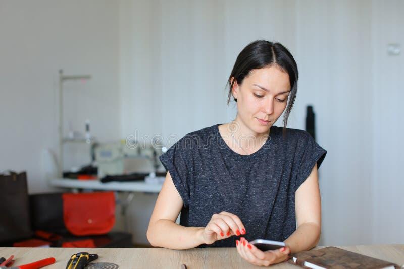Artesana europea que se sienta en el taller y que usa el smartphone, mercancías de cuero hechas a mano imagenes de archivo