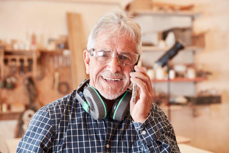 Artesano con el teléfono móvil en el servicio de atención al cliente foto de archivo