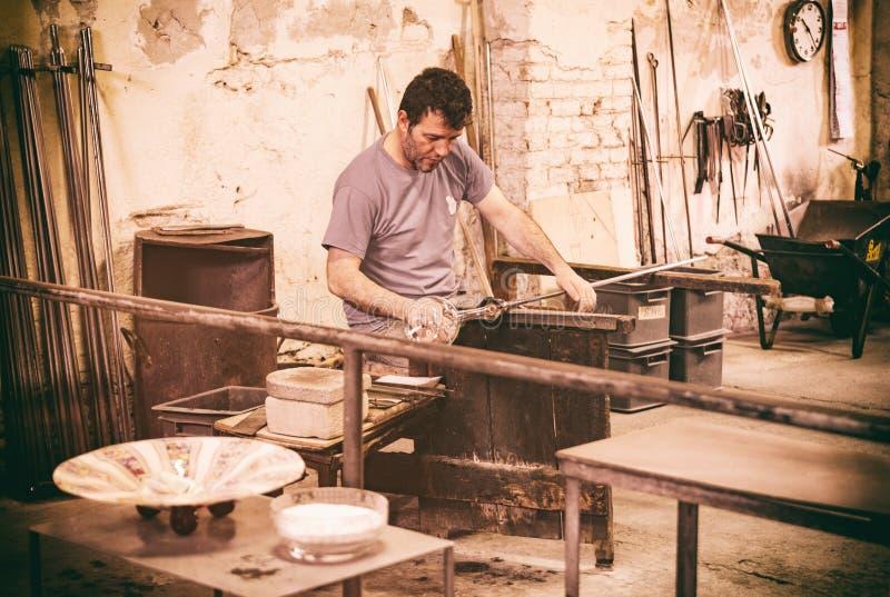 Artesano de Glassblowing en el trabajo en un taller del cristal en Mura fotos de archivo