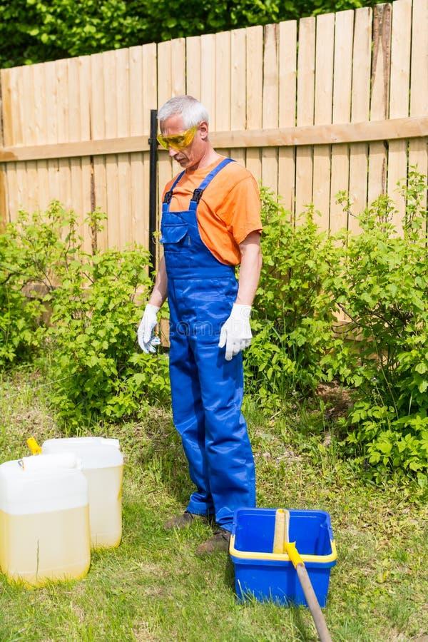 Artesano en el uniforme azul y anaranjado que mira las latas y el cubo de la pintura en el jardín foto de archivo libre de regalías