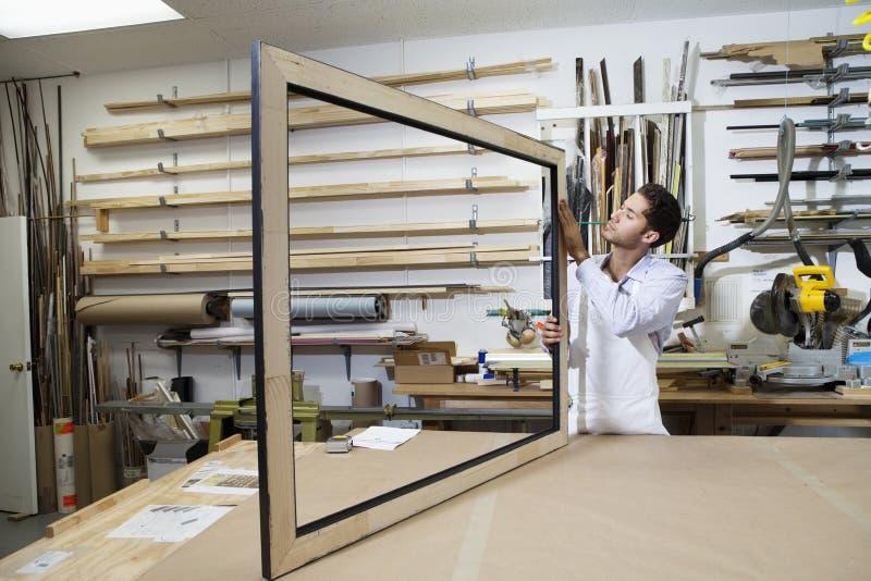 Artesano joven que concentra en la fabricación del marco en taller imágenes de archivo libres de regalías