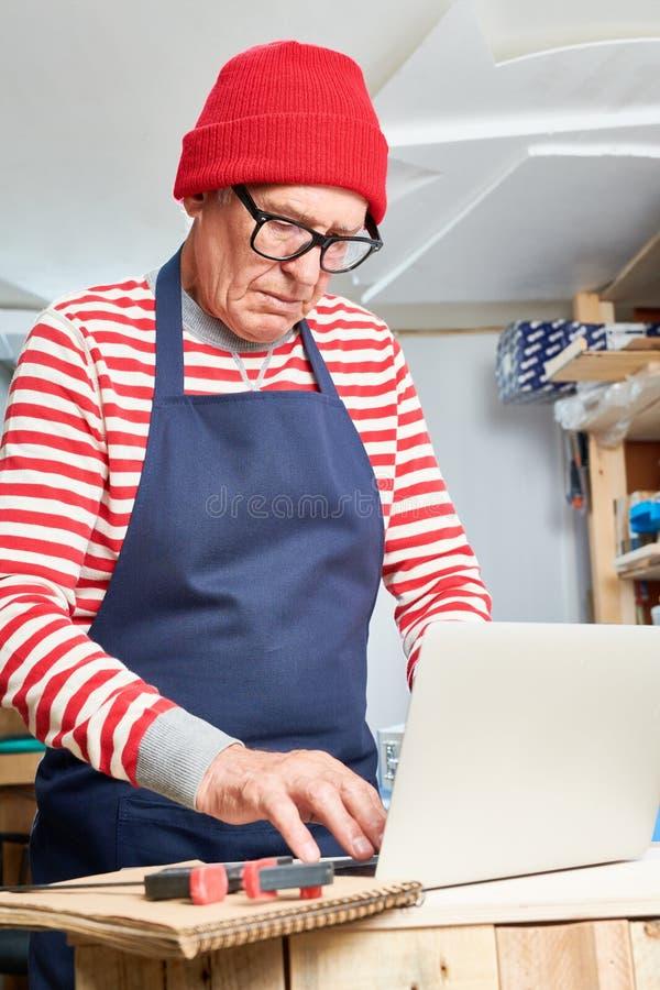 Artesano mayor que usa el ordenador portátil imagenes de archivo