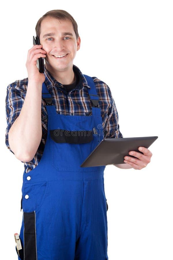 Artesano sonriente con el teléfono móvil y la tableta digital fotos de archivo libres de regalías