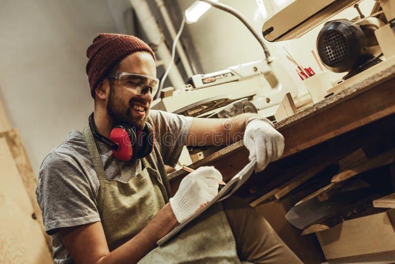 Artesano sonriente que bosqueja cerca del banco de trabajo fotos de archivo libres de regalías