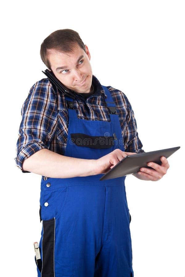 Artesano subrayado con la tableta digital y el teléfono móvil fotos de archivo