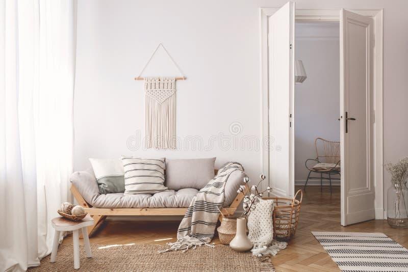 Artesano y decoraciones y accesorios naturales en un interior caliente de la sala de estar con muebles y el suelo de parqué de ma fotografía de archivo libre de regalías