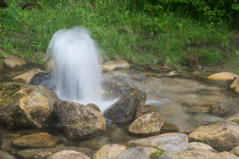 Artesian well. Eruption of spring, natural environment. Stones and water. Clean drinking groundwater erupting out of the ground. stock photos