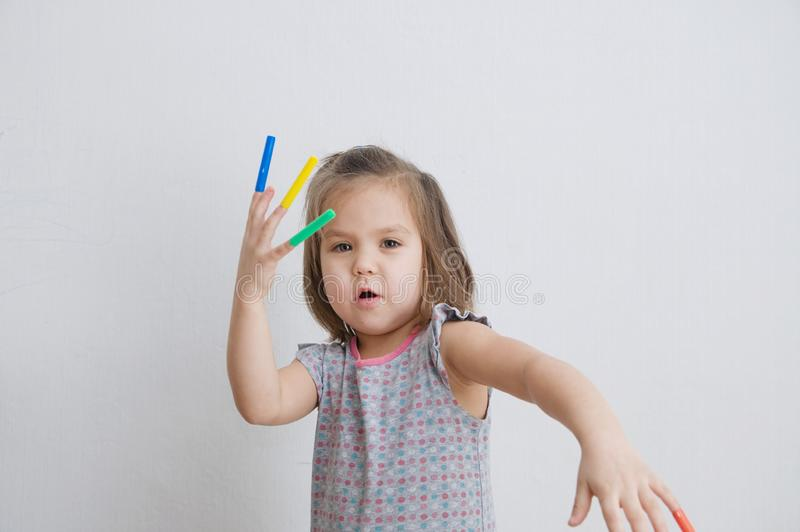 Artful child playing with felt tip pens. baby girl painting and playing. colorful stuff felt pen caps on fingers. Of kid stock photo