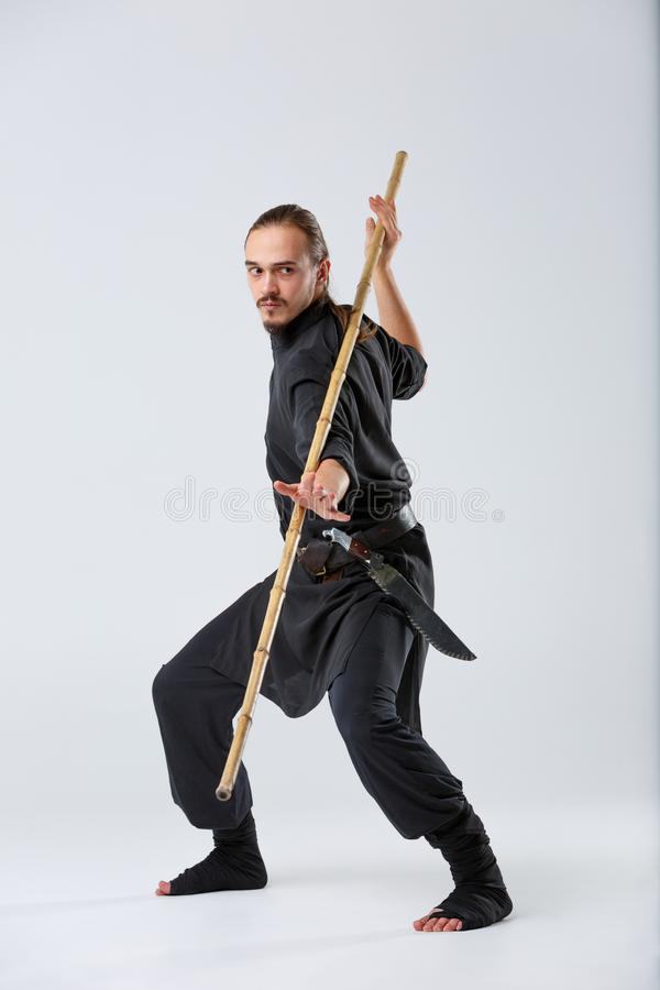 The artful fighter in a black suit, fighting with a long bamboo fighting stick. stock photos
