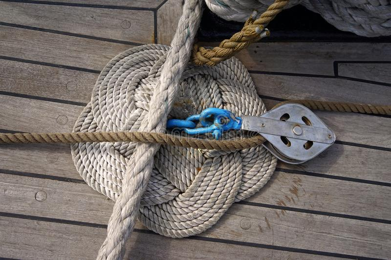 Node on a boat deck. Artfully knotted ropes on a wooden deck of a classic sailboat stock photo