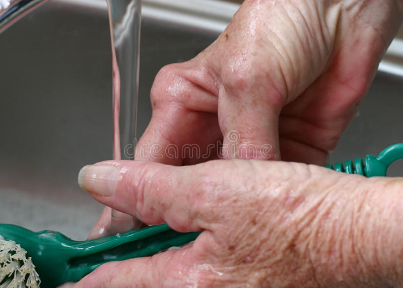 Arthritic hands washing dishes stock photo
