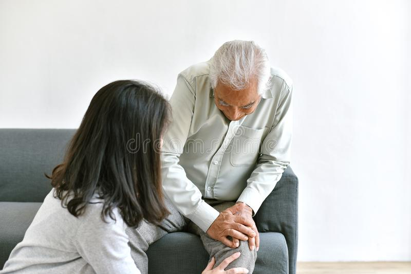Arthritis joint pain problem in old man, Elderly asian man with hand on knee gesture, Daughter frighten and worry about her father. Arthritis joint pain problem stock photo