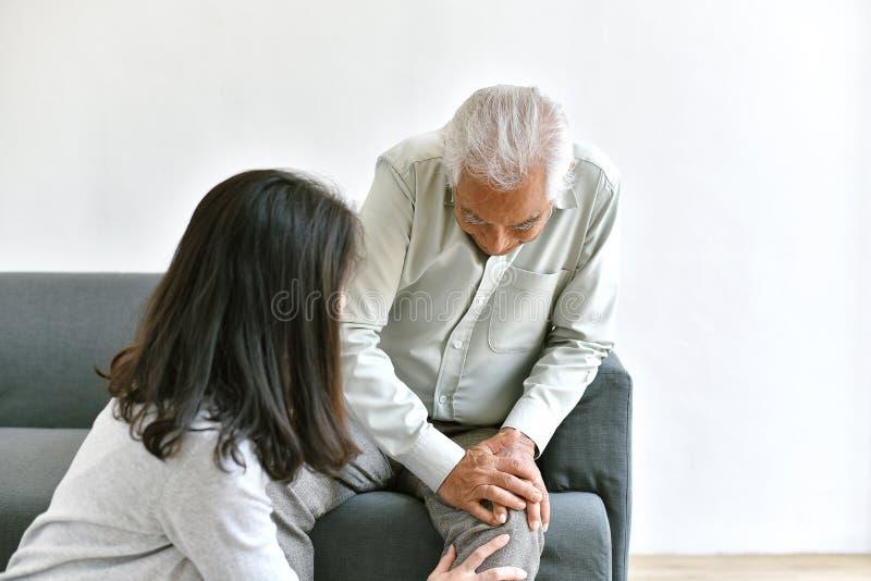 Arthritisgelenkschmerzenproblem im alten Mann, älterer asiatischer Mann mit der Hand auf Kniegeste, Tochter um ihren Vater erschr stockfoto