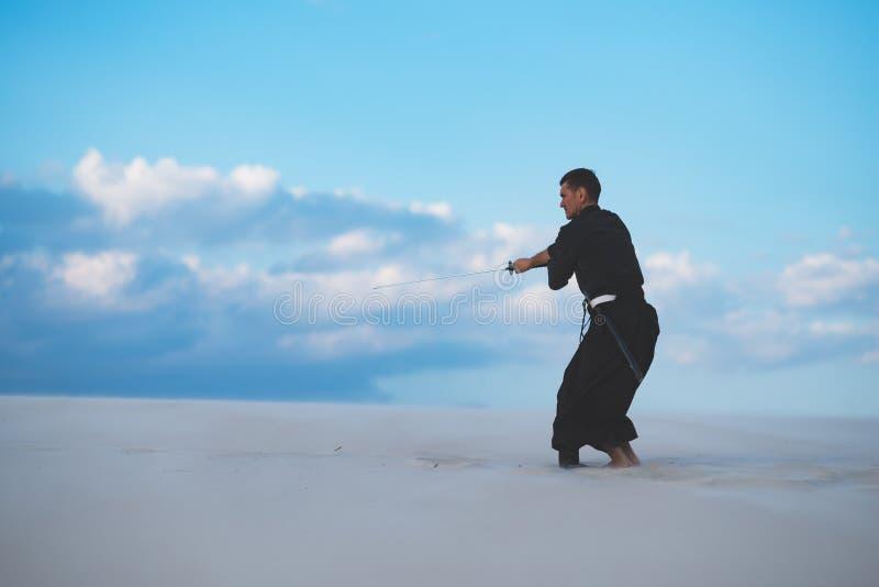 Arti marziali di addestramento dell'uomo in deserto fotografie stock