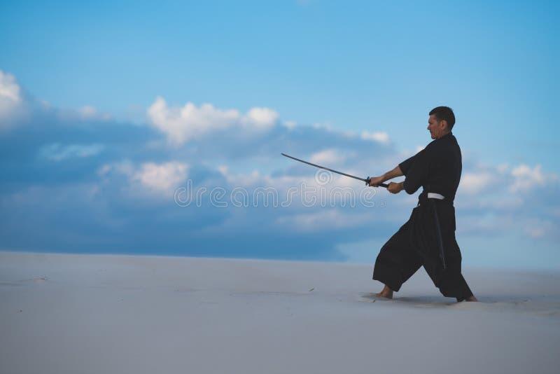 Arti marziali di addestramento dell'uomo in deserto immagine stock