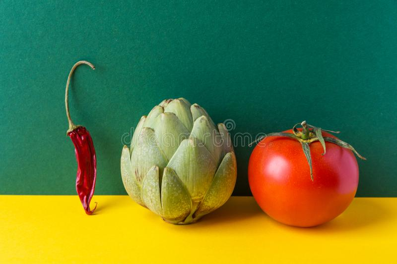 Artichoke ripe juicy tomato hot chili pepper on duotone yellow green background. Creative food poster for Mediterranean cuisine. Healthy plant based vegan diet royalty free stock image