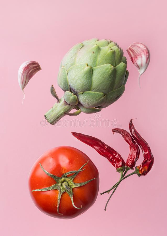 Artichoke ripe juicy tomato hot chili peppers garlic cloves floating levitating on pink background. Creative food poster. Mediterranean cuisine healthy diet royalty free stock photos