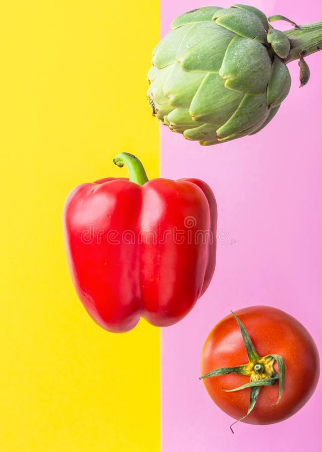 Artichoke ripe juicy tomato red bell pepper floating levitating on duotone yellow pink background. Creative food poster. Mediterranean cuisine healthy diet stock images
