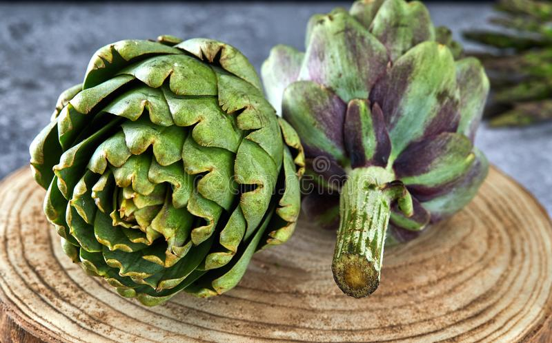 Artichokes with greens on a wooden stand royalty free stock photo