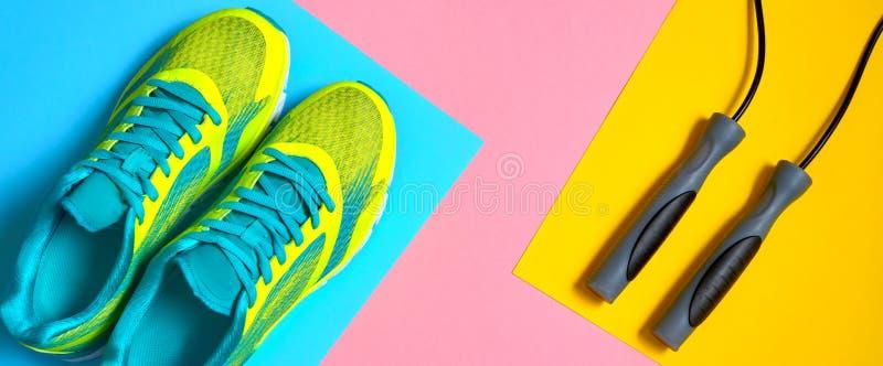Article de sport avec les chaussures de course et corde à sauter sur le fond en pastel de rose, bleu et jaune, l'espace de copie  images stock