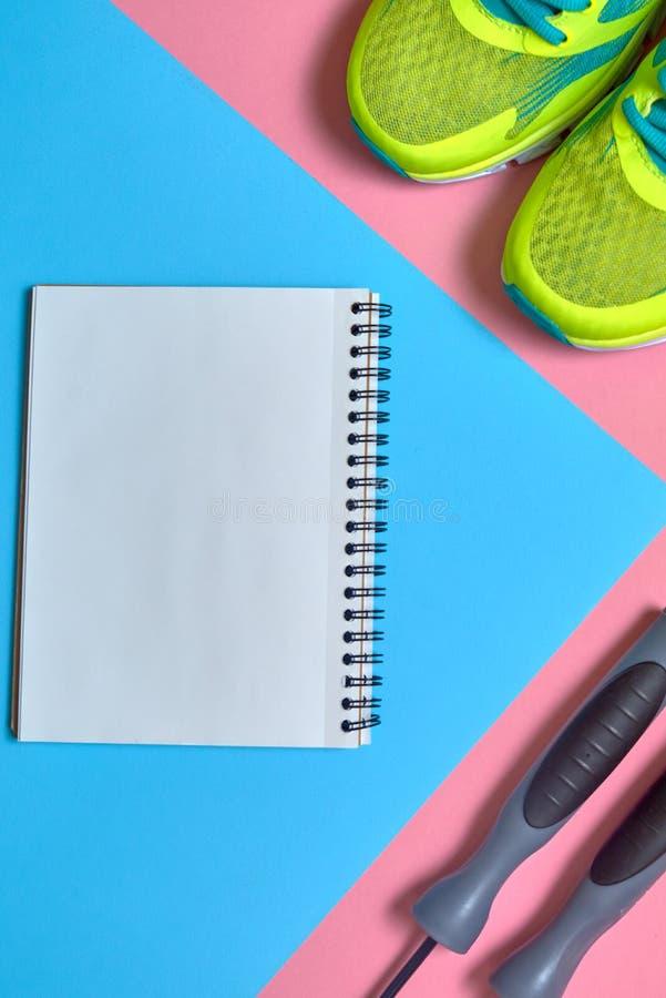 Article de sport avec les chaussures, la corde à sauter et le carnet vide sur le rose et le fond en pastel bleu, l'espace de copi photo libre de droits