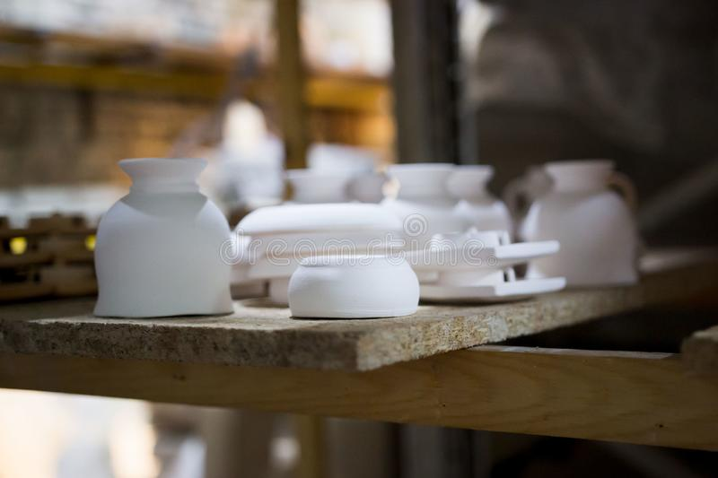 Articles of clay made by slip forming using plaster molds a master with 13 years of experience. drying on a rack with. Shelves from chipboard. glasses, plates royalty free stock image
