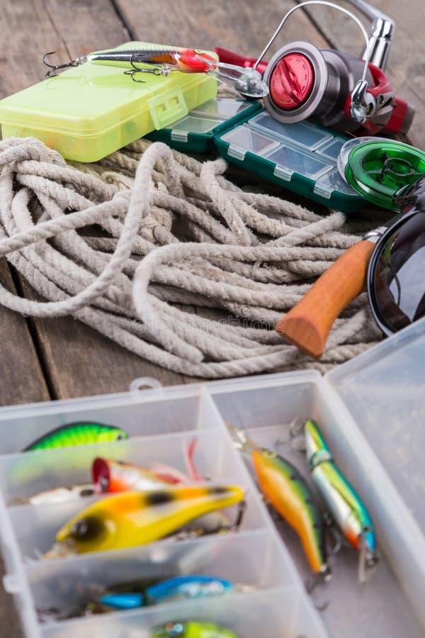Articles de pêche et amorces dans des boîtes de rangement photo stock