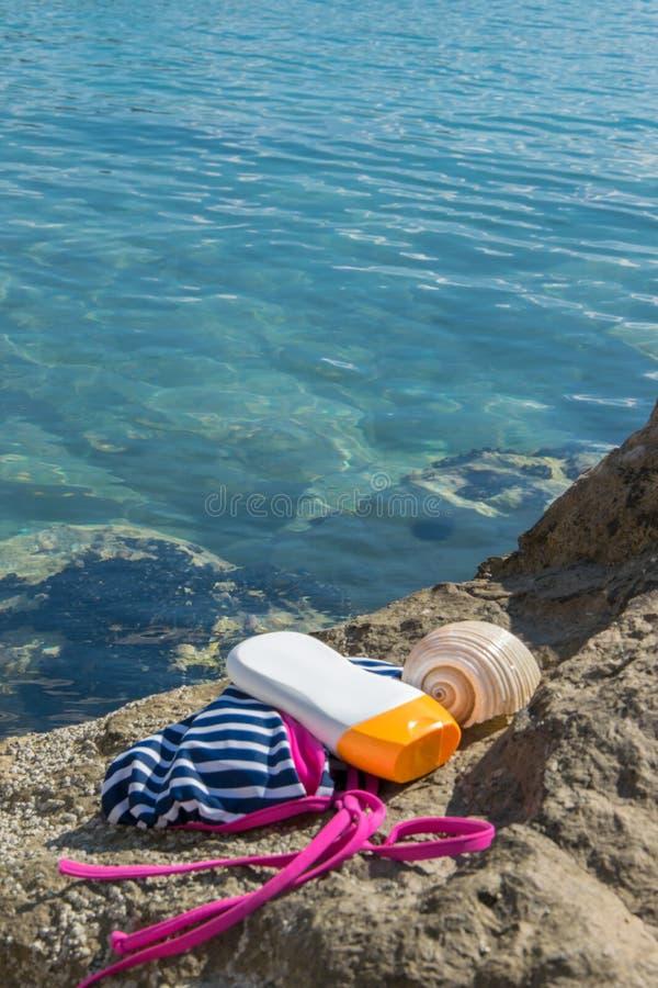 Articles de plage - vêtements de bain, crème de protection du soleil et une coquille sur une roche de bord de la mer images stock