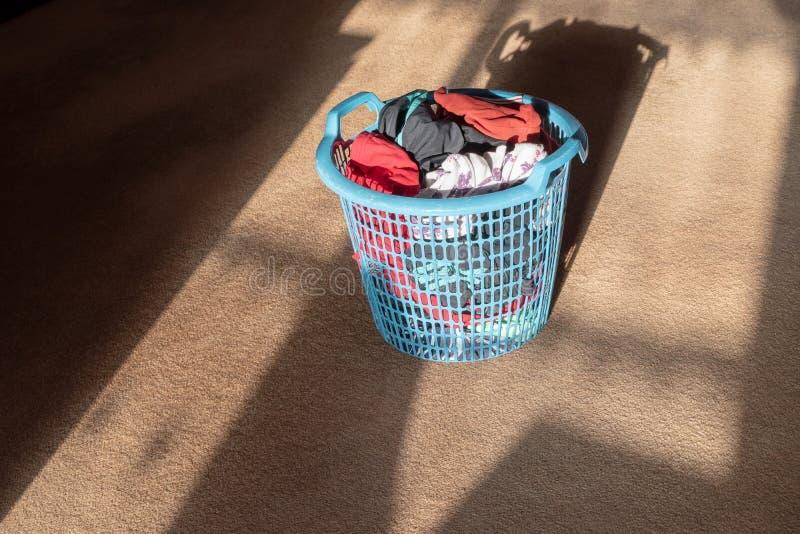 Articles fraîchement blanchis d'habillement à l'intérieur d'un panier à linge en plastique bleu photo libre de droits