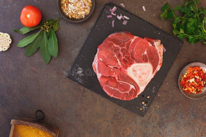 Articolazione fresca del vitello sulla pietra e sui condimenti dell'ardesia immagini stock