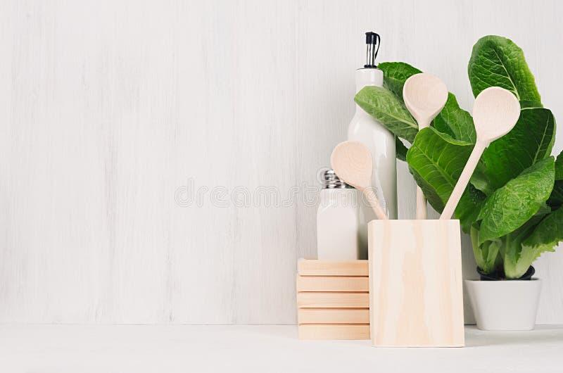 Articolo da cucina di legno beige naturale e pianta verde su fondo di legno bianco leggero, spazio della copia immagini stock