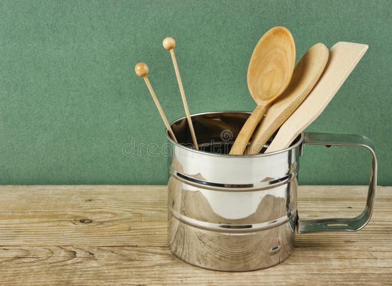 articolo da cucina di legno in brocca del metallo sulla vecchia tavola di legno sopra fondo verde fotografia stock libera da diritti