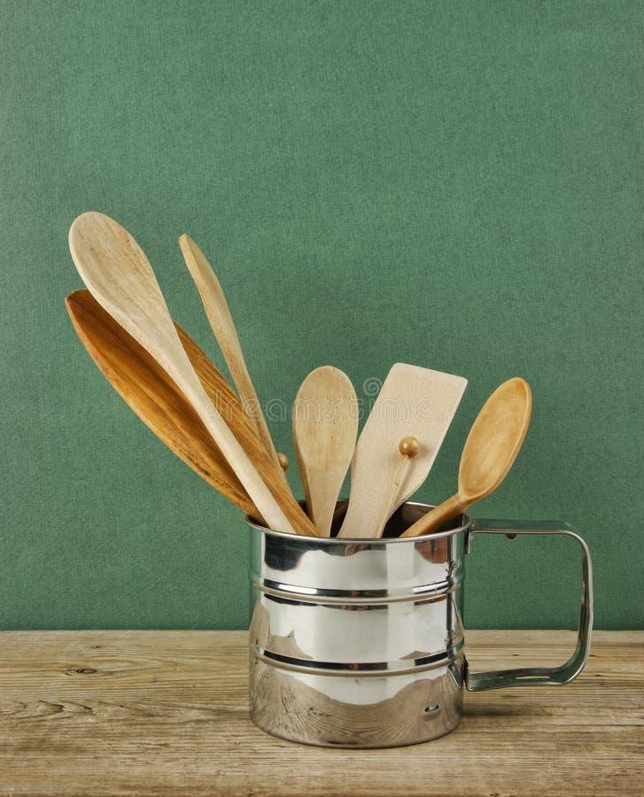 articolo da cucina di legno in brocca del metallo sulla vecchia tavola di legno sopra fondo verde immagini stock libere da diritti