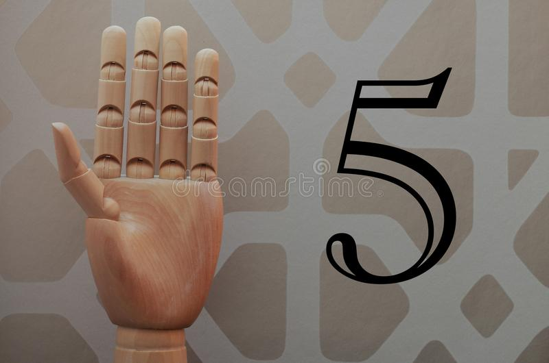 Articulated wooden hand with five fingers raised in allusion to number five stock image