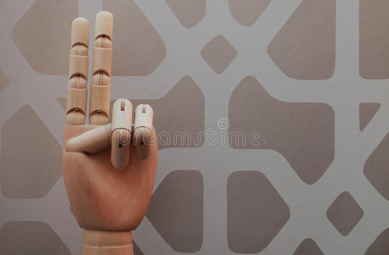 Articulated wooden hand with two fingers raised in allusion to number two stock photo