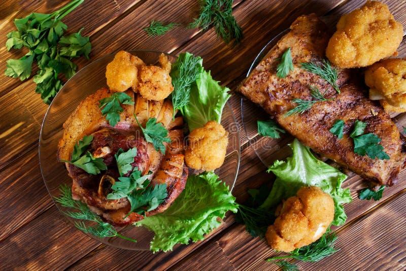 Articulation et nervures frites d?licieuses de porc, laitue et persil, chou-fleur et aneth dans des plats transparents Viande cui photo libre de droits