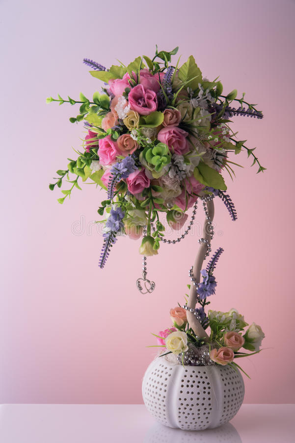 Artificial bouquet of diffirent beautiful small flowers with nice silver chain and two hanging hearts. Flower pot stock image