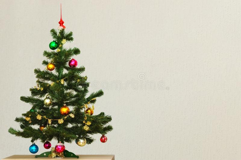 Artificial Christmas tree. Artificial green Christmas tree with colorful Christmas toys, standing on a table against a gray wall stock photography