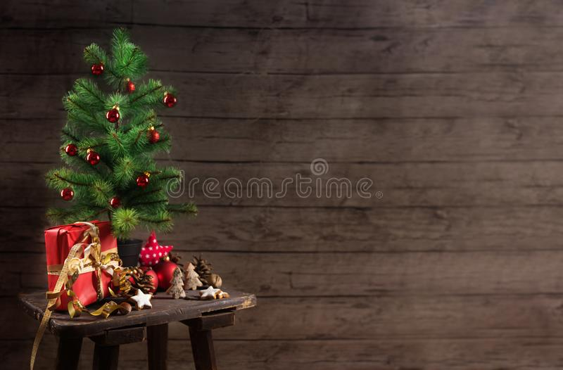 artificial christmas tree with red baubles, gift box and decoration on an small table in front of a rustic wooden wall, generous royalty free stock photos