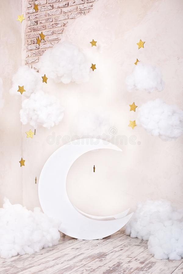 Artificial decorations with a moon and stars. Vintage decorations. Stylish vintage children`s room with a wooden moon and textile. Clouds. vintage children`s royalty free stock images