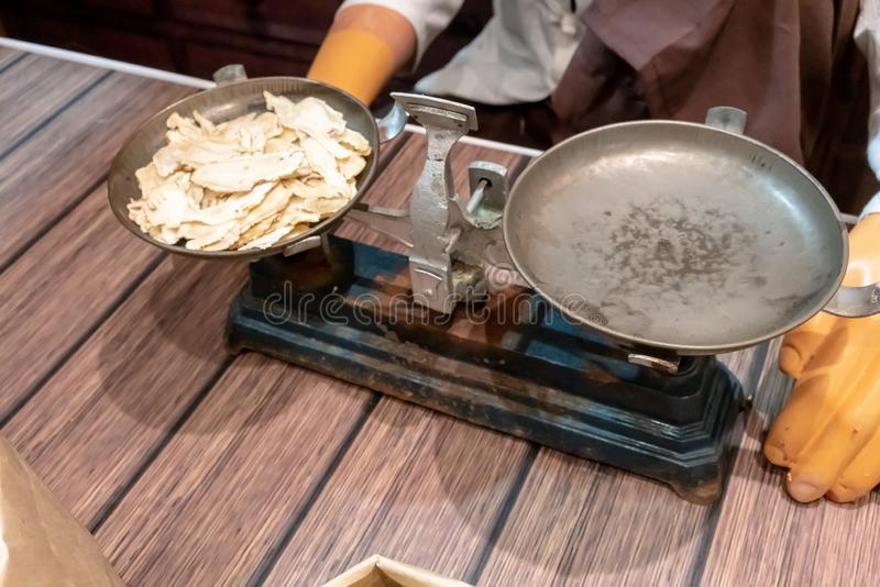 Artificial dried Ginseng slices in antique metal weighing balance pan royalty free stock photography