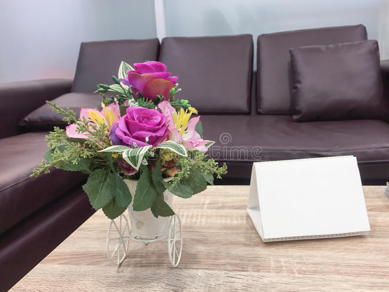 Artificial flower vase on table top. And pillow on sofa stock photography