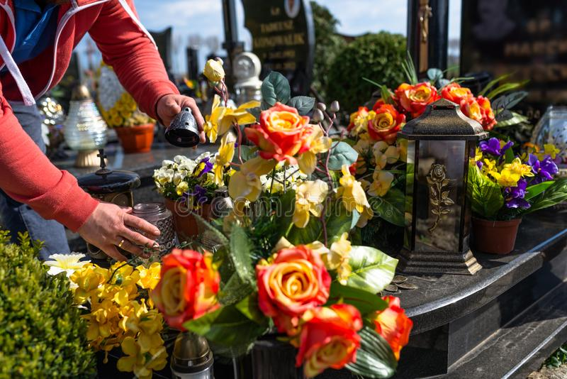 Artificial flowers and candlesticks lie on the tombstone in the cemetery, visible hands of a man. stock images