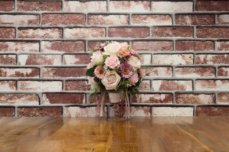 Artificial flowers put on terrace wood with brick wall in vintage style stock images