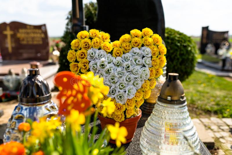 Artificial flowers in the shape of a heart and candlesticks lie on the tombstone in the cemetery. stock photos